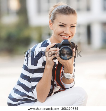 Portrait of a beautiful young blond woman with a camera, lifestyle. female photographer with professional SLR camera, natural light. Beautiful smiling girl with camera on nature