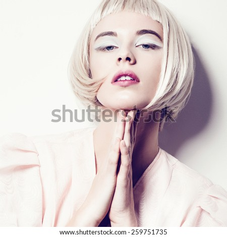 Portrait of a beautiful young blond woman with short hair in studio on a white background, concept of beauty, close up - stock photo