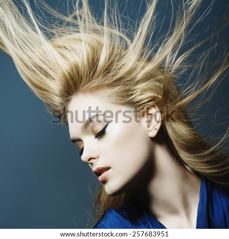Portrait of a beautiful young blonde woman in studio on a blue background with developing hair - stock photo