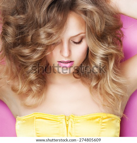 Portrait of a beautiful young blonde woman in the studio on a pink background in a yellow dress, the concept of beauty and health - stock photo