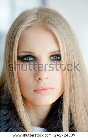 Portrait of a beautiful young blonde woman with blue eyes - stock photo