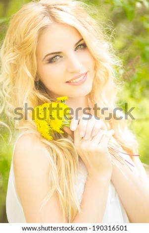 Portrait of a beautiful young blonde woman with dandelions. Girl posing in nature and smiling - stock photo