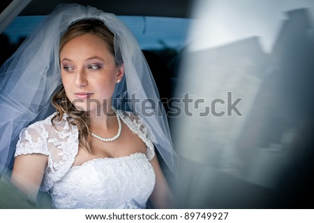 Portrait of a beautiful young bride waiting in the car on her way to the wedding ceremony - stock photo