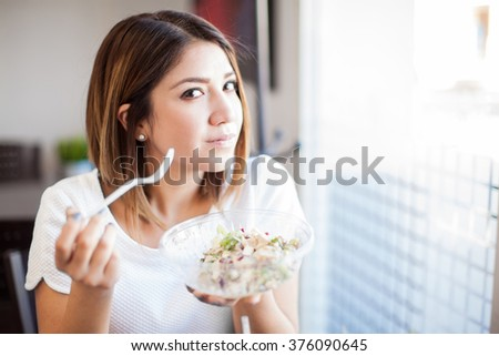 Portrait of a beautiful young brunette eating a salad at a restaurant and making eye contact - stock photo