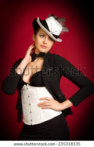 portrait of a beautiful young brunette girl in a white hat on a red background - stock photo