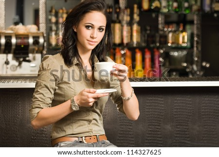 Portrait of a beautiful young brunette having her coffee. - stock photo