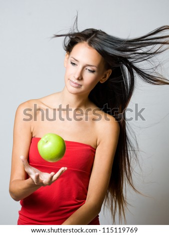 Portrait of a beautiful young brunette juggling fresh apple. - stock photo