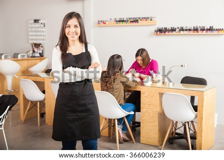 Portrait of a beautiful young brunette standing in front of her nail salon and smiling - stock photo