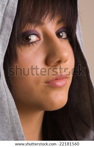 Portrait of a beautiful young brunette with sweater and hood - stock photo