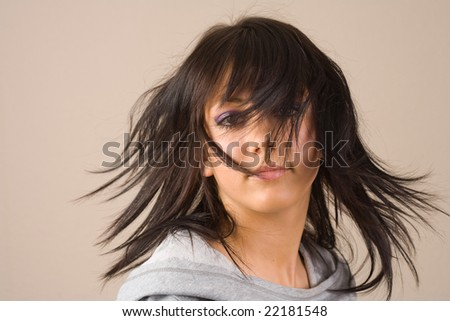 Portrait of a beautiful young brunette with sweater flipping her hair - stock photo