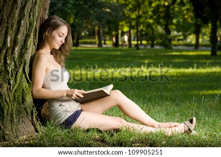 Portrait of a beautiful young brunette woman enjoying book outdoors. - stock photo