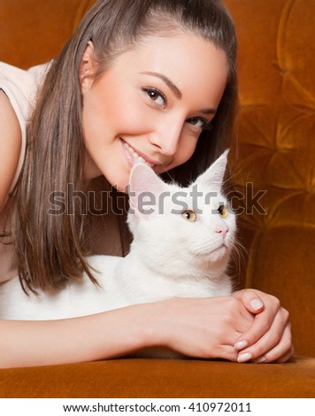 Portrait of a beautiful young brunette woman having fun with cat.