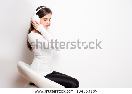 Portrait of a beautiful young brunette woman listening to music in headphones. - stock photo