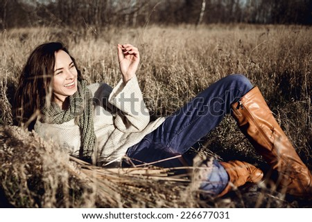Portrait of a beautiful young brunette woman lying in a field in autumn, life style - stock photo