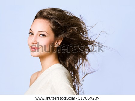 Portrait of a beautiful young brunette woman on blue background. - stock photo