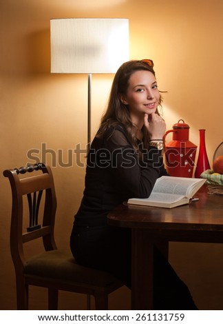 Portrait of a beautiful young brunette woman reading a book. - stock photo