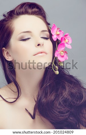 Portrait of a beautiful young brunette woman. Wearing long loose curly hair, posing with a pink flower. Against grey studio background. Spa concept - stock photo