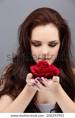 Portrait of a beautiful young brunette woman. Wearing long loose curly hair, posing with a red flower. Against grey studio background. Spa concept - stock photo
