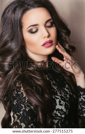portrait of a beautiful young brunette woman with long hair with closed eyes and a gorgeous makeup - stock photo