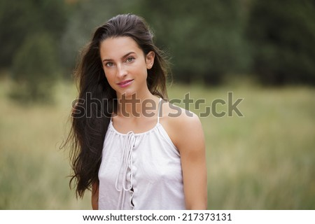 Portrait of a beautiful young brunette young lady with a sassy smile - stock photo