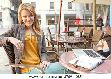 Portrait of a beautiful young business woman at coffee shop terrace with laptop computer, smiling at the camera. Professional smiling woman drinking coffee using technology, outdoors lifestyle.
