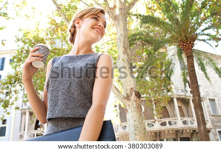 Portrait of a beautiful young business woman commuter walking in classic city, holding a coffee paper cup turning back. Professional businesswoman drinking coffee, on the go lifestyle exterior. - stock photo