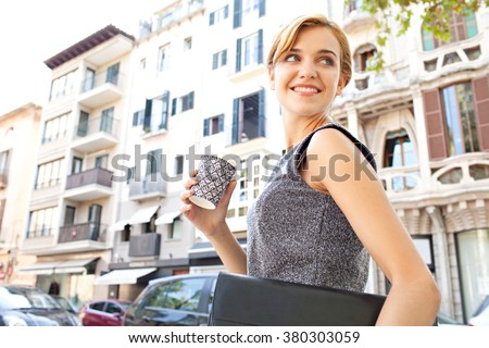 Portrait of a beautiful young business woman commuter walking in classic city, holding coffee paper cup turning back, smiling. Professional businesswoman drinking coffee, on the go lifestyle exterior. - stock photo