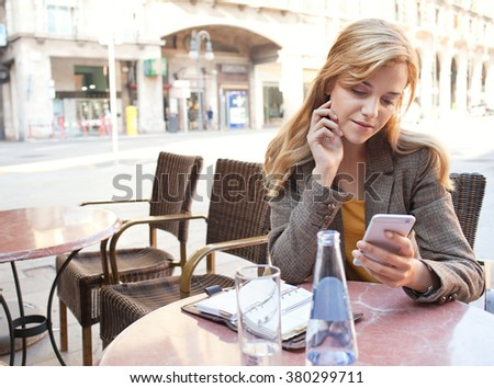 Portrait of a beautiful young business woman sitting at a coffee shop terrace with a laptop computer, using a smart phone to work. Professional thoughtful woman using technology, outdoors lifestyle. - stock photo