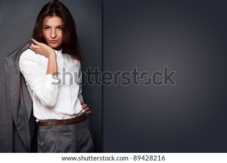 Portrait of a beautiful young business woman standing with hand holding jacket behind her shoulder against grey background and posing fashionable. Looking at camera. Special Copyspace - stock photo
