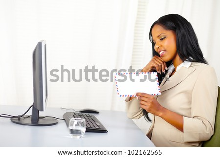 Portrait of a beautiful young businesswoman at work looking to a letter - stock photo