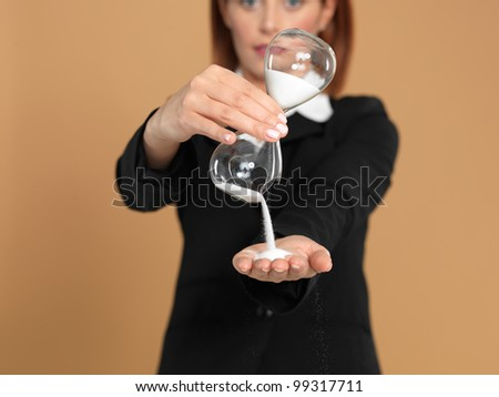 portrait of a beautiful, young businesswoman, holding a broken hourglass in her hands, on beige background