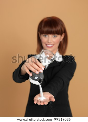 portrait of a beautiful, young businesswoman, holding a broken hourglass in her hands, on beige background - stock photo