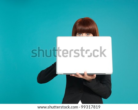 portrait of a beautiful, young businesswoman, holding a laptop in front of her, with her eyes showing, on blue background
