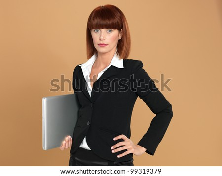 portrait of a beautiful, young businesswoman, holding a laptop, smiling, on beige background - stock photo