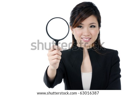 Portrait of a beautiful young businesswoman holding and looking at magnifying glass, isolated on white. - stock photo