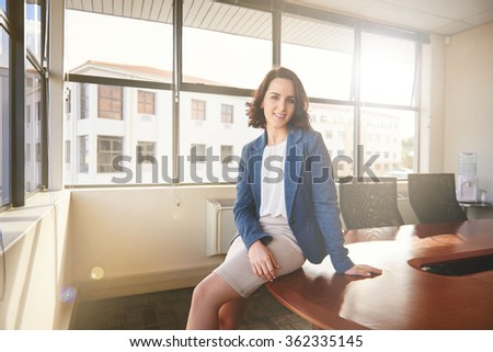Portrait of a beautiful young businesswoman looking relaxed and confident while sitting on the edge of a table in an empty boardroom with large windows through which soft evening sunflare is shining - stock photo