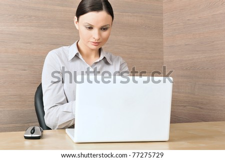 Portrait of a beautiful young businesswoman on the computer, working. Office background. - stock photo