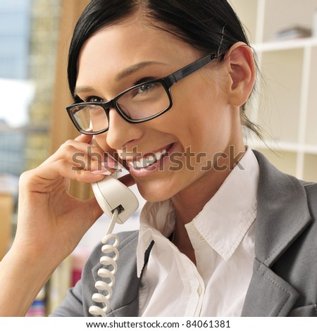 Portrait of a beautiful young businesswoman on the phone and happy. Office background. - stock photo