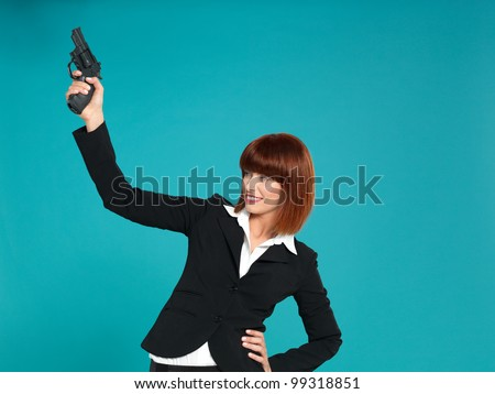 portrait of a beautiful, young businesswoman, pointing a gun in the air, to start a compettion, on blue background - stock photo