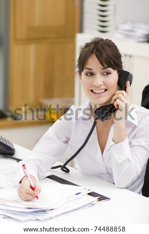 Portrait of a beautiful young businesswoman using phone in office - stock photo