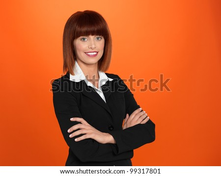 portrait of a beautiful, young, businesswoman, with her arms crossed, on orange background
