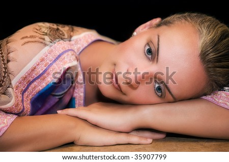 Portrait of a beautiful young caucasian woman resting on her arms and thinking - stock photo