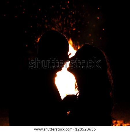 Portrait of a beautiful young couple about to kiss against fire in the night