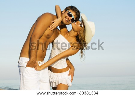 Portrait of a beautiful young couple against blue sky background - stock photo