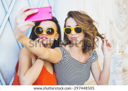 portrait of a beautiful young couple fashionable girls blonde and brunette in a bright yellow dress and sunglasses posing and smiling for the camera  and makes a smartphone selfi - stock photo