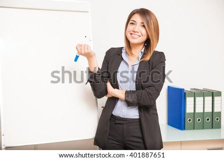 Portrait of a beautiful young English teacher ready to write on a board and teach her class - stock photo