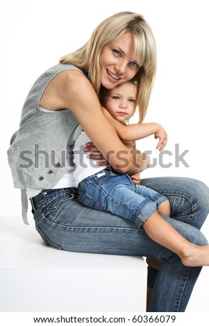 Portrait of a beautiful young family - mother and her baby smiling. Mother and little daughter in denim - stock photo