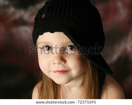 Portrait of a beautiful young female child model wearing a black crochet hat posing - stock photo
