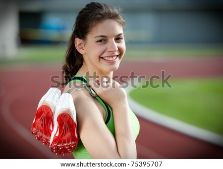 Portrait of a beautiful young female sprinter standing on a running track and holding her sprinting shoes with spikes - stock photo