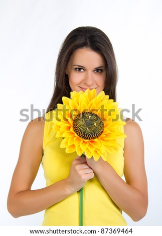 portrait of a beautiful young female with a sunflower - stock photo